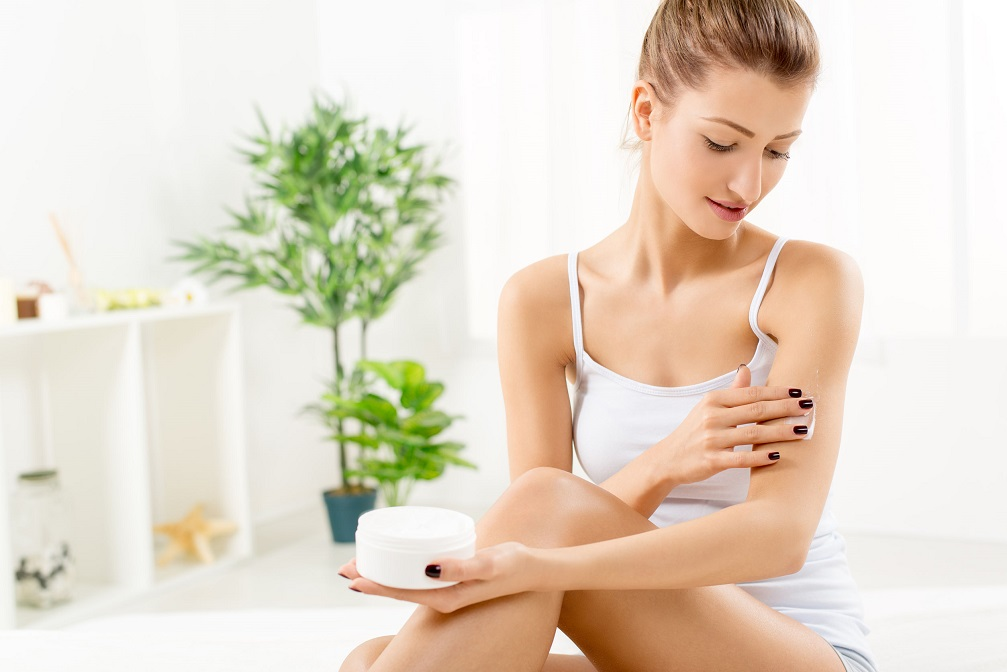 39336254 - beautiful young woman applying body lotion.