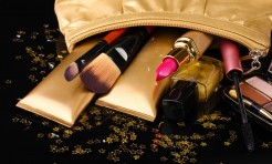 14035221 - beautiful golden makeup bag and cosmetics isolated on black