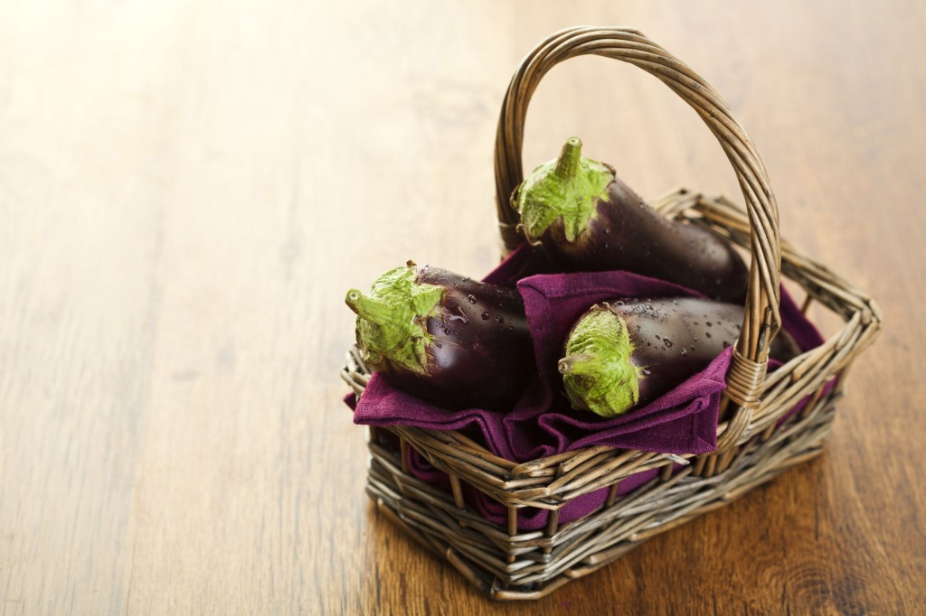 14953903 - raw aubergines or eggplants in basket on wooden backround.