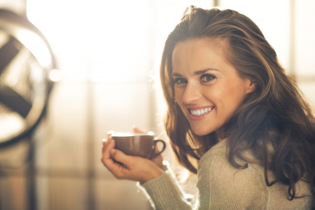 33561030 - portrait of happy young woman with cup of hot beverage