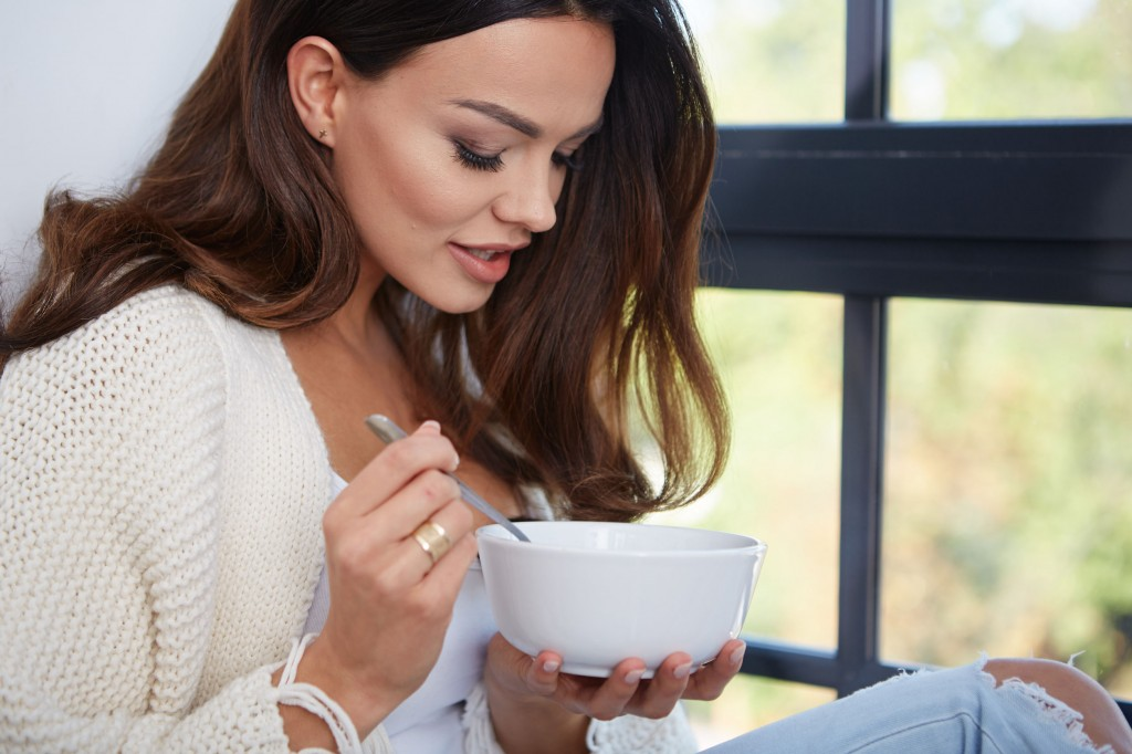 47428964 - young woman eating soup by the window.