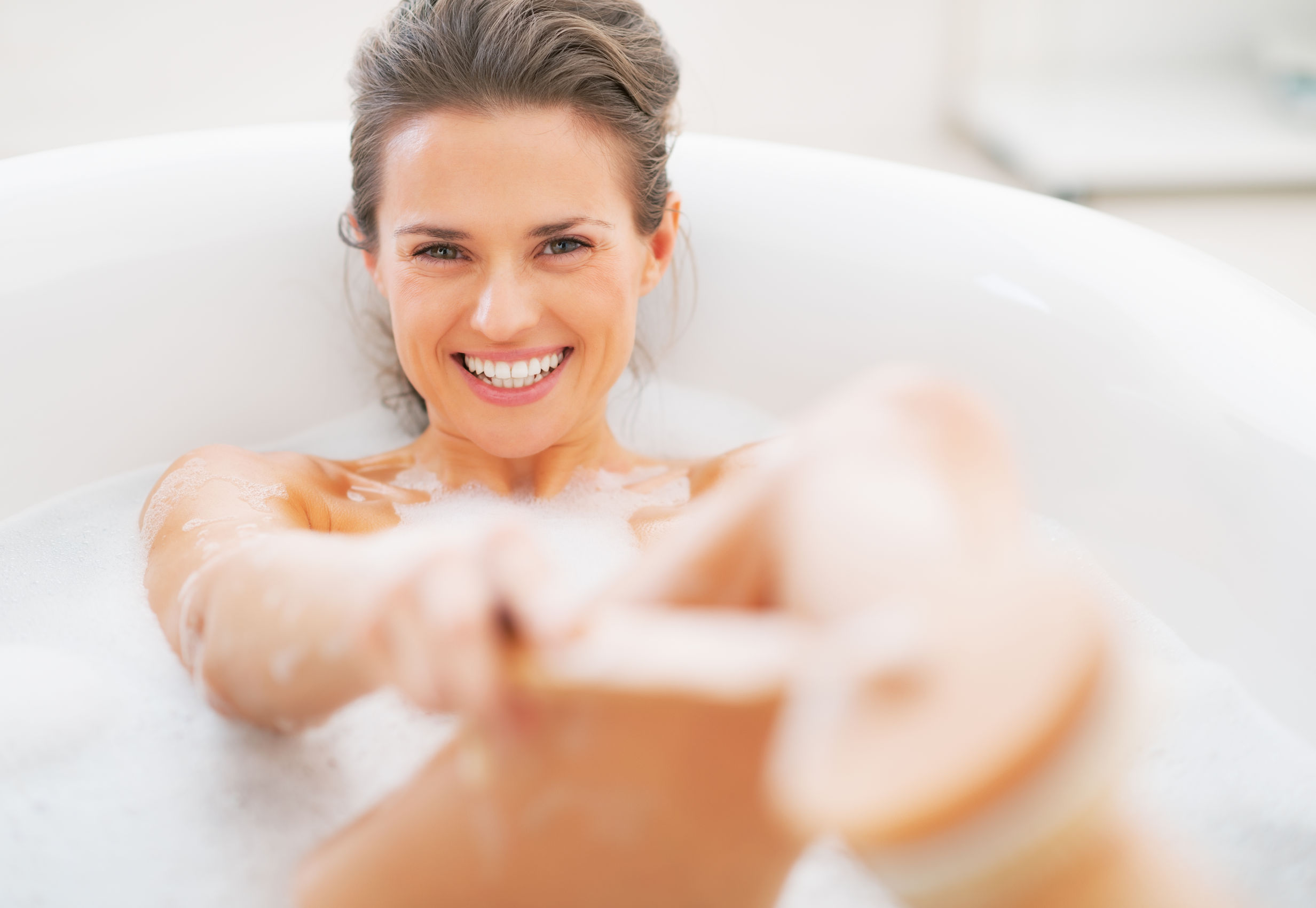 24824087 - smiling young woman washing with body brush in bathtub