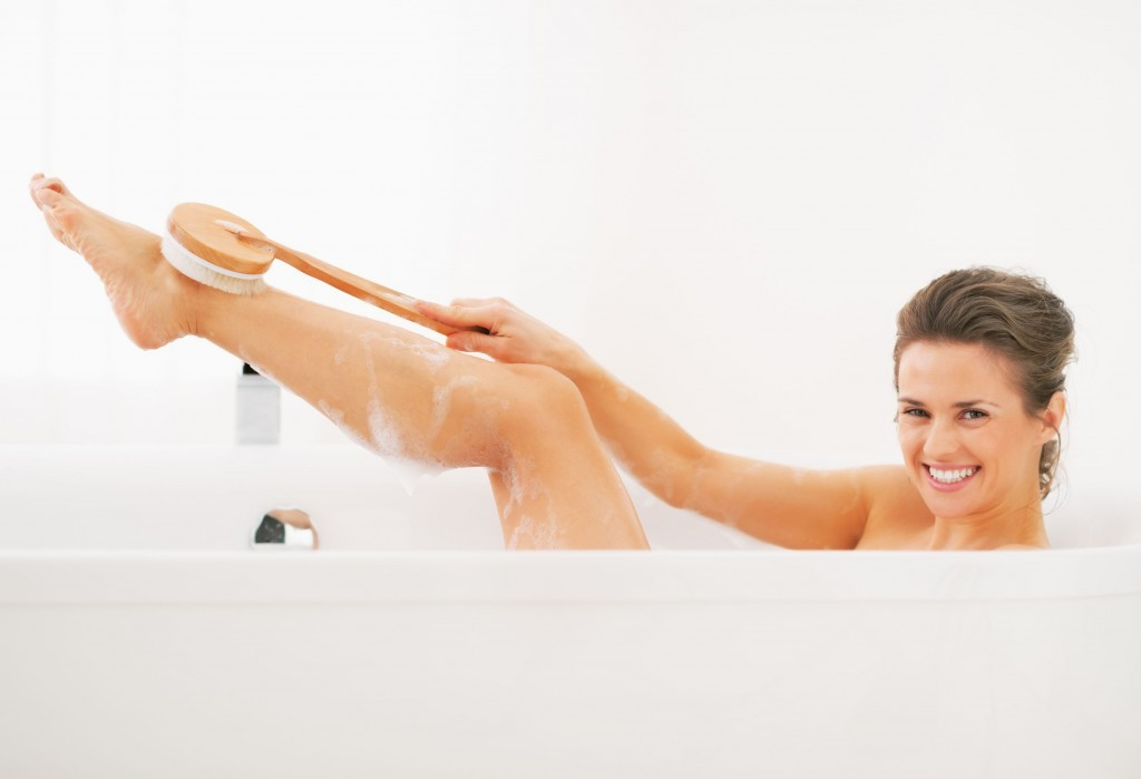 24824114 - happy young woman washing with body brush in bathtub