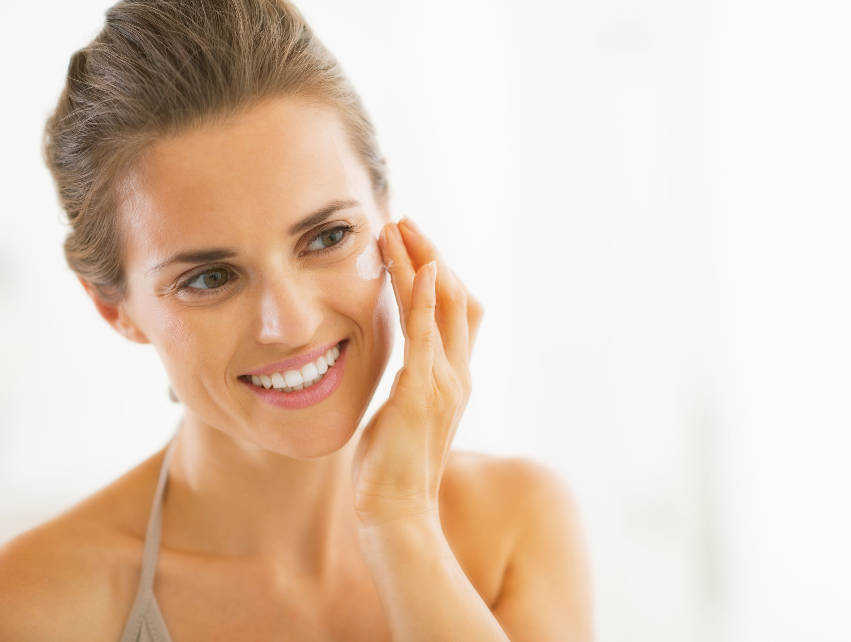 25078426 - portrait of happy young woman applying cream in bathroom
