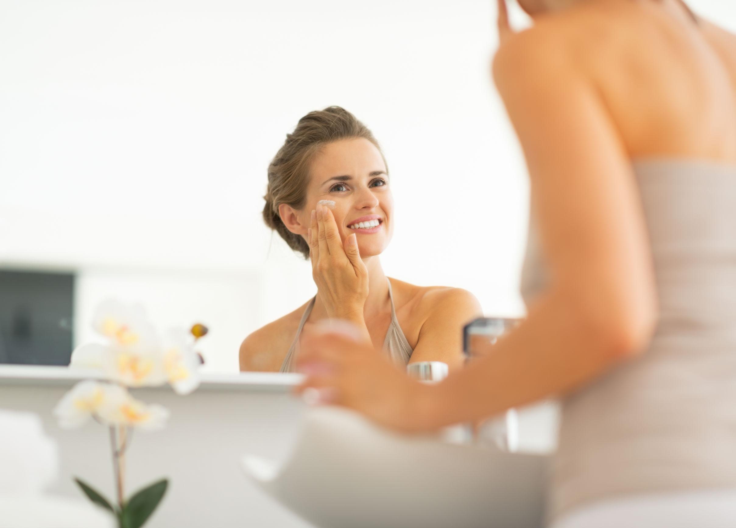 29004541 - happy young woman applying cream in bathroom