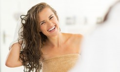 29038858 - portrait of smiling young woman wiping hair with towel