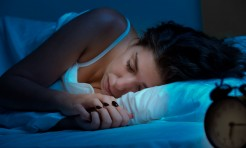 33444664 - woman sleeping in a bed in a dark bedroom