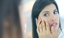 40644098 - beautiful brunette girl looking at skin in mirror