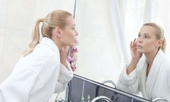 22528141 - woman in bathrobe looks at the mirror in bathroom
