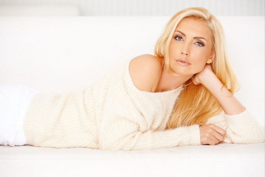 22579966 - the white sweatshirt is worn by a blonde lady  she lying on sofa