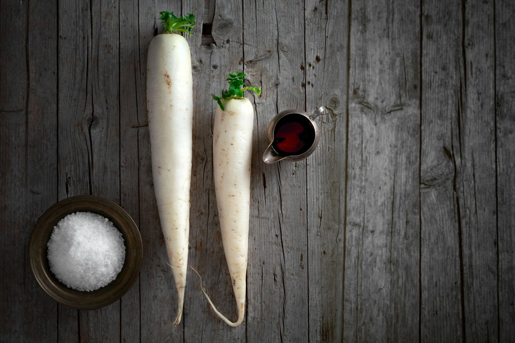 39243037 - daikon radish on wooden background, above view.