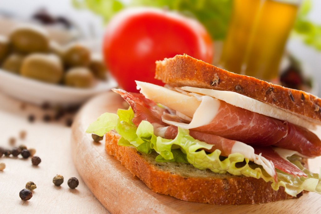 10635500 - prosciutto and cheese sandwich with olives and lettuce.