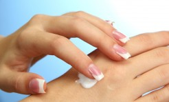 15958817 - beautiful woman hands with cream, on blue background
