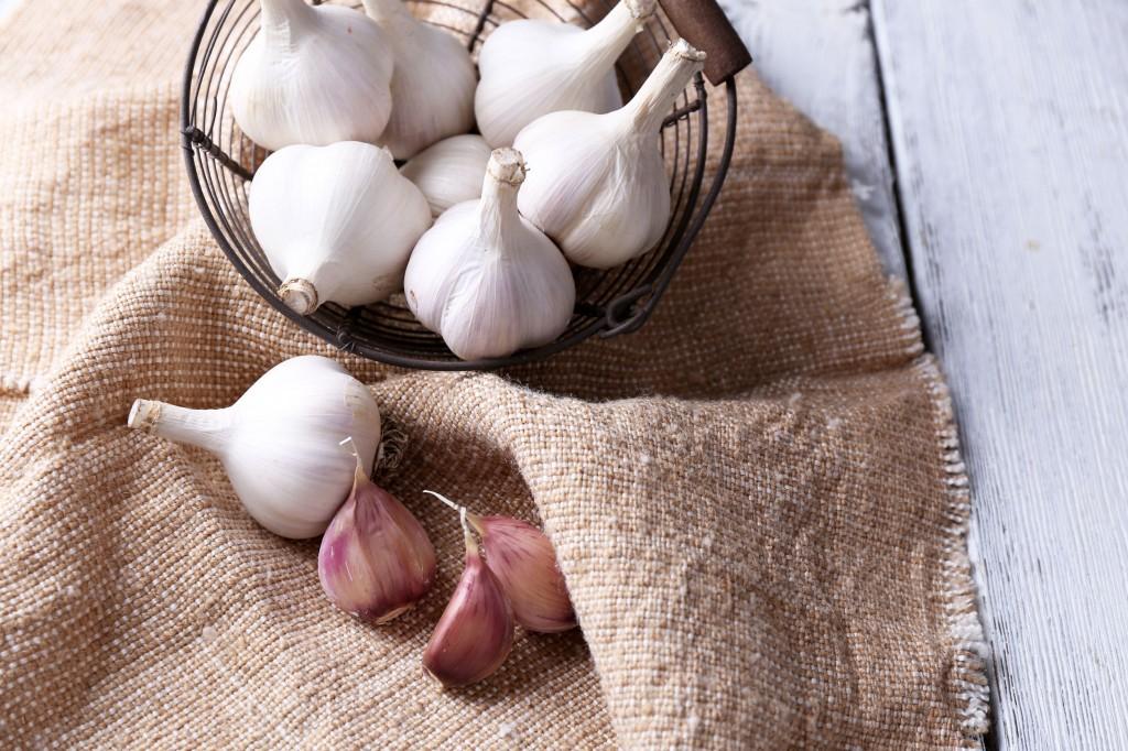 31138746 - fresh garlic in basket, on wooden background