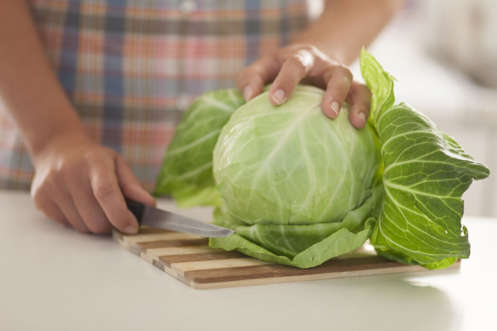 35085385 - green cabbage on cutting board in kitchen.