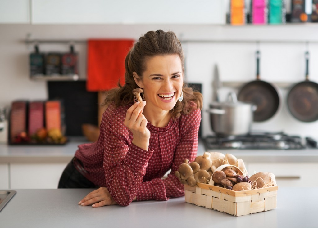36070893 - happy young housewife with basket with mushrooms in kitchen