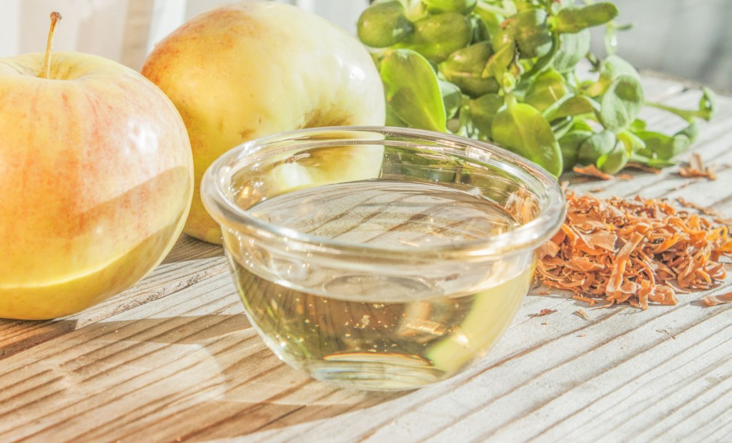 40894546 - yellow apple vinegar in a glass bowl, between apples and herbs
