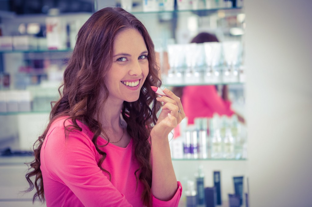44408201 - pretty woman trying a lipstick at the pharmacy