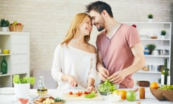 49526157 - young couple cooking fresh vegetarian salad together