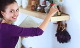 50053785 - young woman reading cookbook in the kitchen, looking for recipe