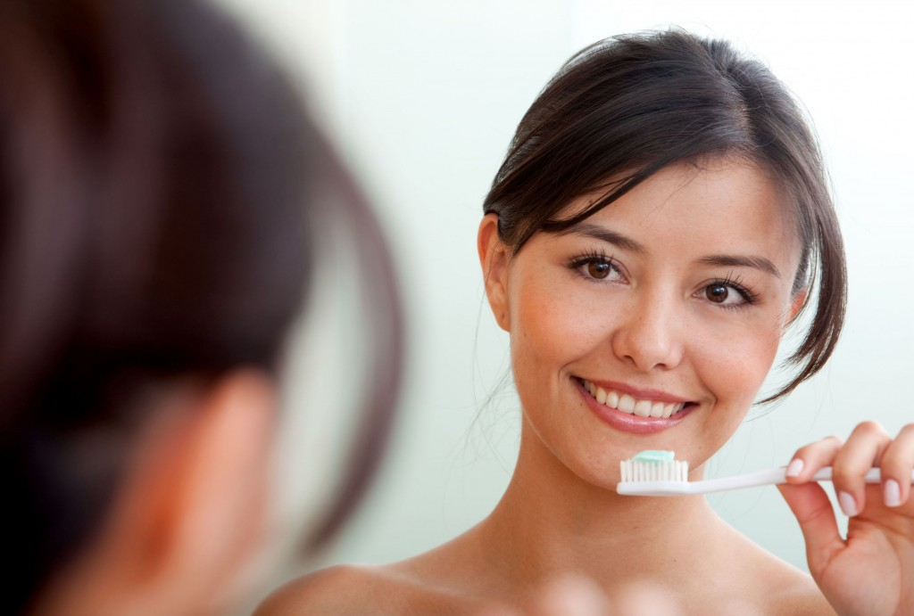 6825304 - woman in front of a mirror brushing her teeth
