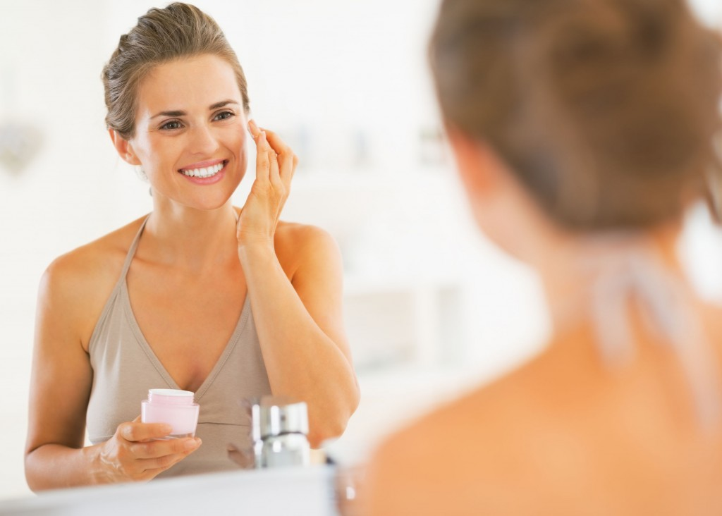 25078424 - happy young woman applying cream in bathroom