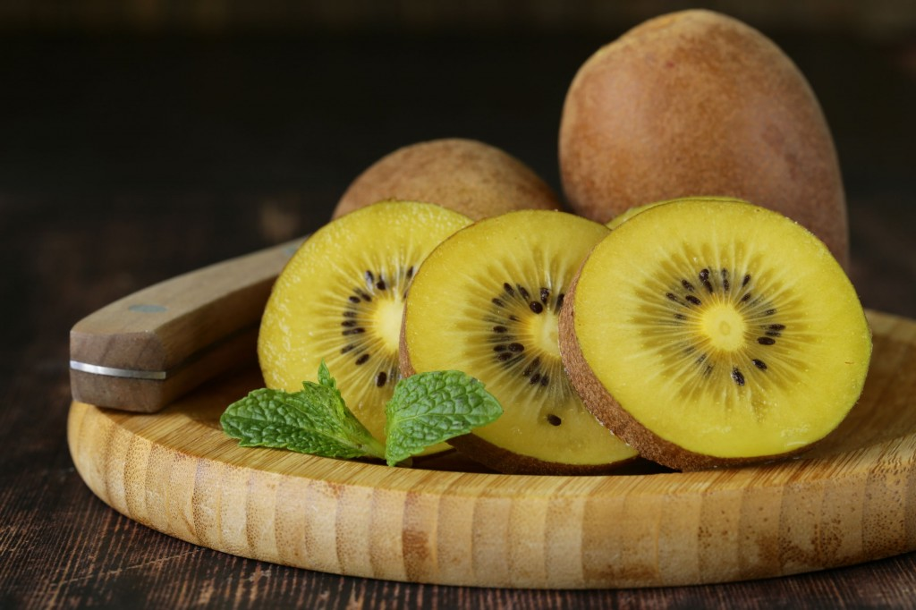 27941363 - ripe yellow kiwi on a wooden board