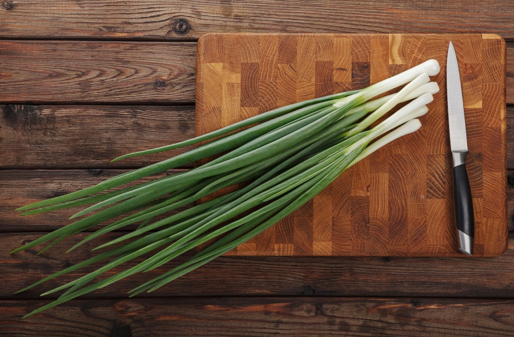 47259060 - top view of spring onions bunch ready to cutting on chopping board
