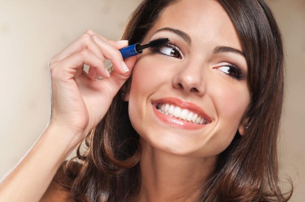 10451804 - beautiful smiling woman applying mascara on her eyelashes
