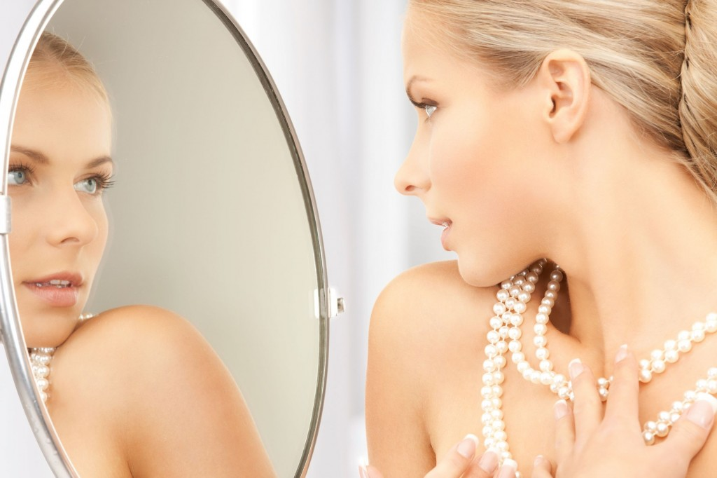 20772408 - woman with pearl necklace looking in the mirror