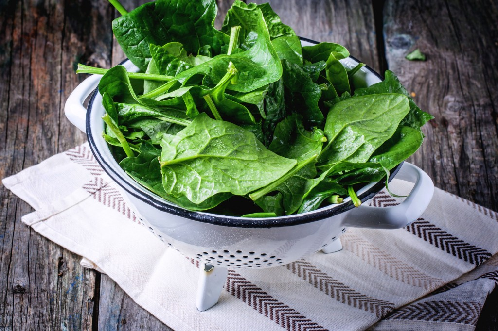 27447801 - fresh spinach in metal colander over wooden background