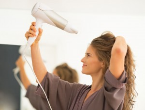 27698530 - young woman blow drying hair in bathroom