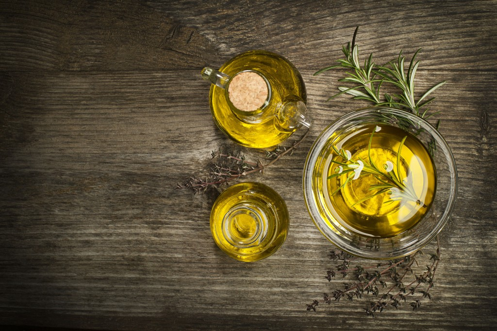 50122491 - olive oil with fresh herbs on wooden background.