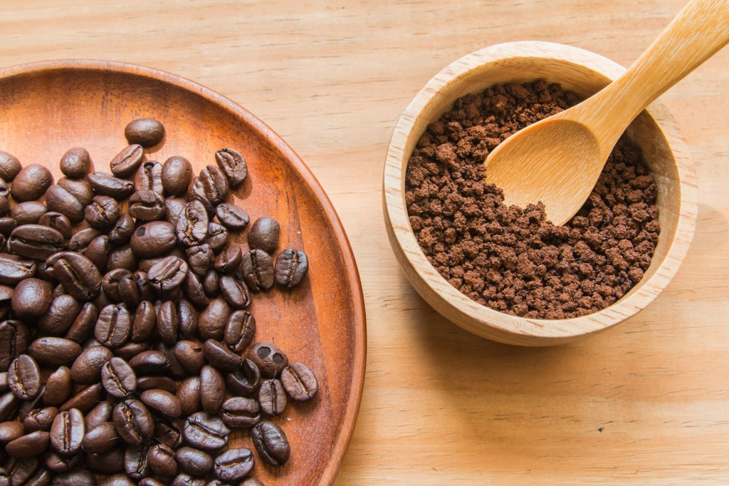 55608346 - coffee beans on wood dish with instant coffee in wood bowl