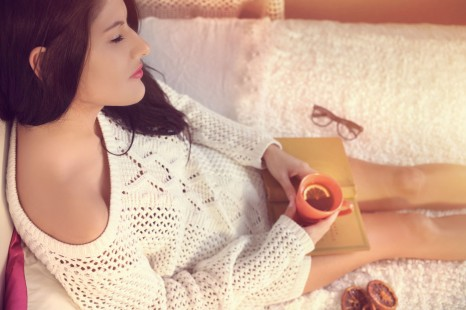 32304786 - young girl in a white sweater drinking tea with lemon