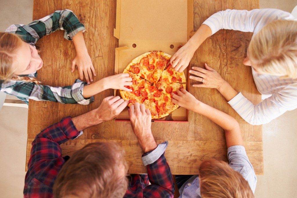 41461574 - family eating pizza together, overhead view