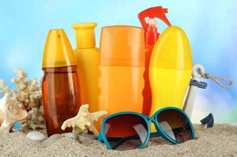 22252315 - bottles with suntan cream and sunglasses, on blue background