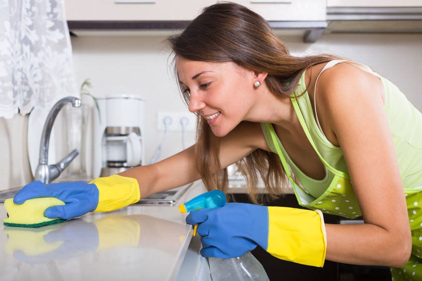 33559700 - young  happy woman in apron cleaning kitchen sink at home