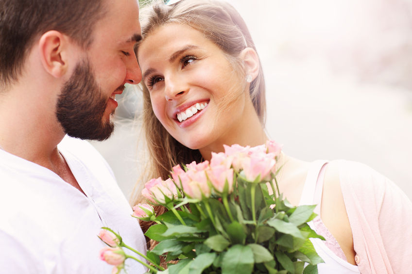 42863480 - a picture of a young romantic couple with flowers in the city