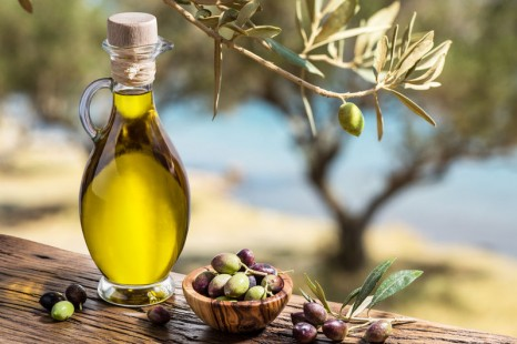 49883726 - olive oil and berries are on the wooden table under the olive tree.