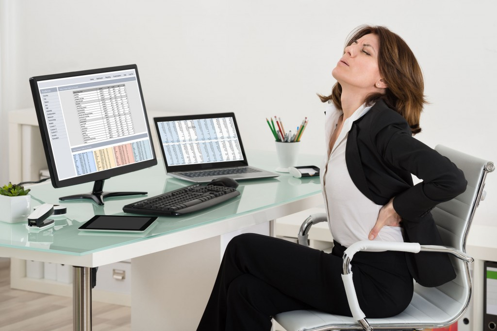 52952123 - businesswoman suffering from backache while working in office