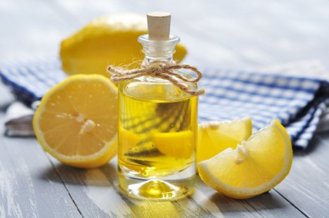 21356191 - lemon oil in a glass bottle with fresh lemon on wooden background
