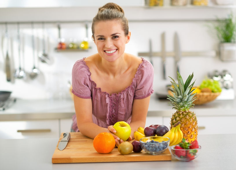 31040774 - portrait of young housewife with fruits in modern kitchen