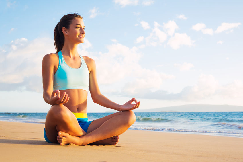 31135006 - young woman practicing yoga on the beach at sunset.