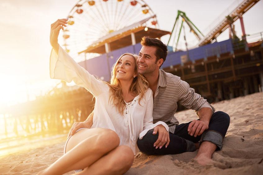 37647054 - happy romantic couple taking selfie at santa monica