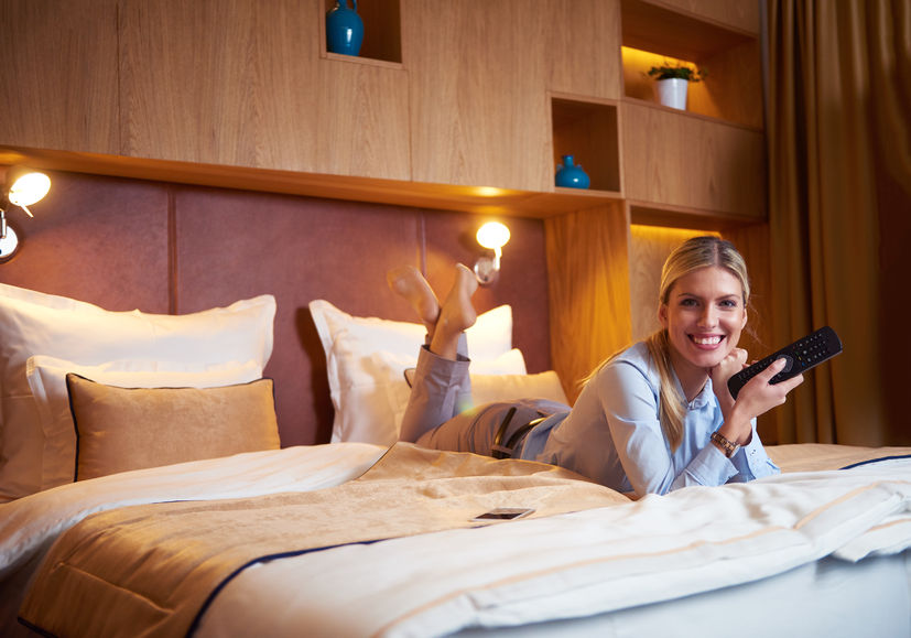 45775382 - young business woman relaxing in hotel room and looking tv