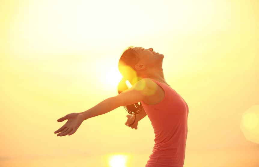 50960300 - woman open arms under the sunrise at sea
