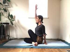 左手はお尻の横で床を支えます。息を吸いながら右手を上げます。