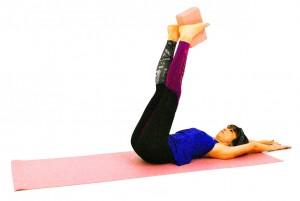 床に仰向けになり、吐く息とともにお腹を腰に引き寄せ、ドローイングします。次にクッションなどを挟みます。ドローイング状態をキープしたまま、両手は頭の先に伸ばし、両足も天井方向に引き上げます。