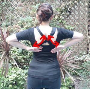 背筋を伸ばし、両手で腰下の背骨をさすります